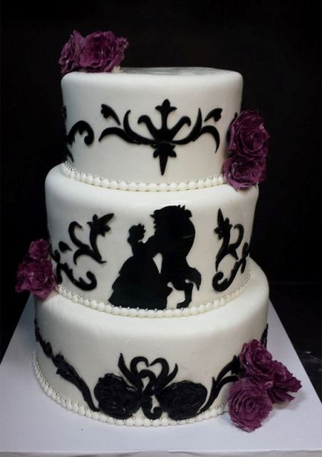 a black and white The Beauty and The Beast wedding cake with purple blooms and beads on each layer