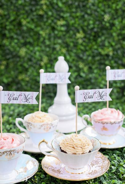 cupcakes served in vintage teacups and with little toppers styled as Alice in Wonderland