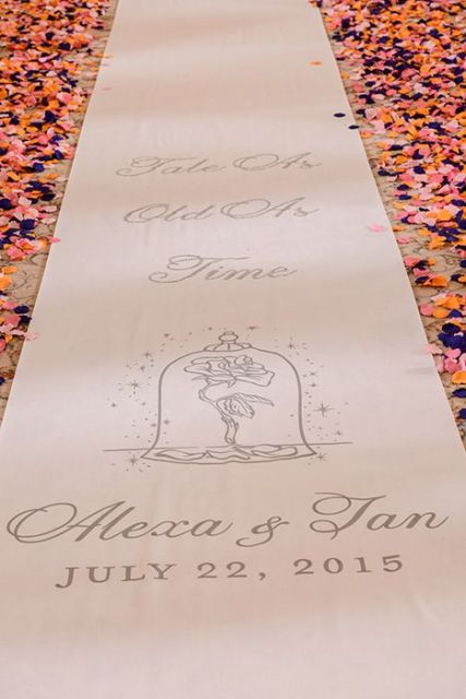 a wedding aisle runner with calligraphy, your wedding date and names plus petals looks very Disney-like