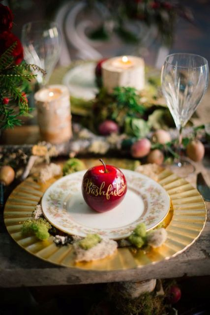 a chic place setting with a gold charger with moss on it, a red apple with calligraphy for a Snow White hint