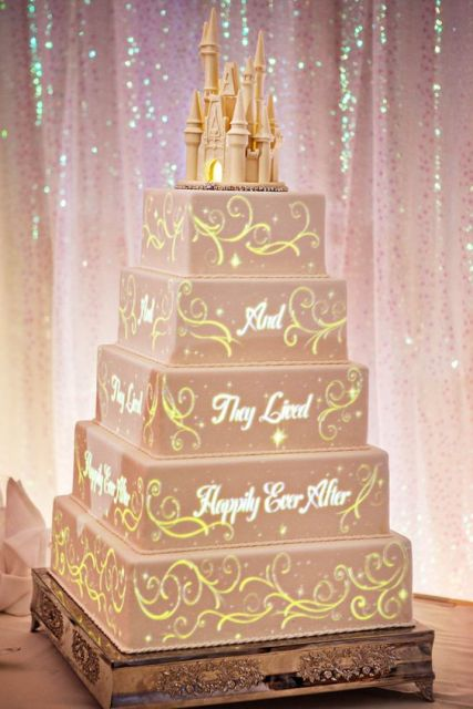 a very tall blush square wedding cake with traditional cartoon decor and a castle topper