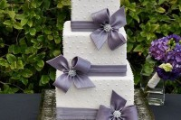 an elegant white square wedding cake with beads and edible ribbons and bows in grey