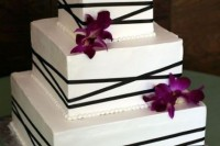 a white square wedding cake wth black ribbons and purple orchids for a tropical wedding