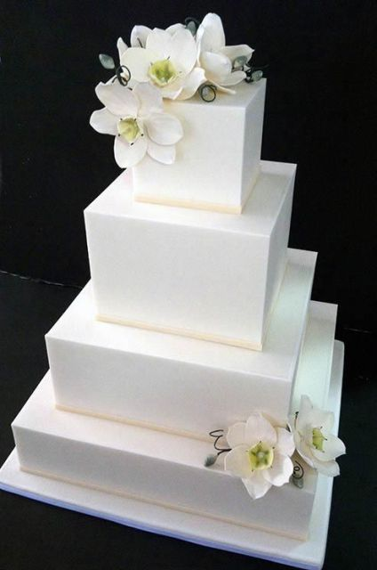 a minimalist white square wedding cake with white orchids is a timelessly elegant idea