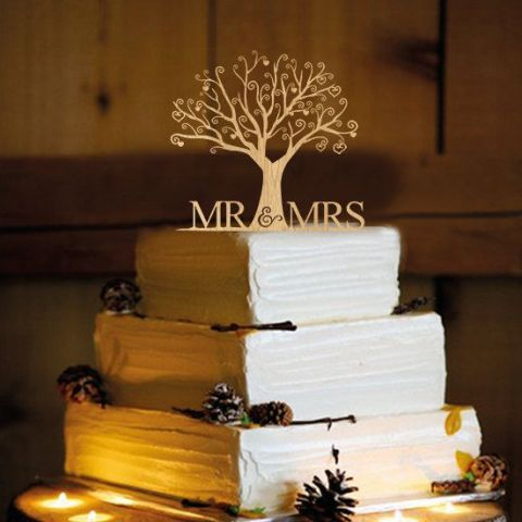 a white textural wedding cake topped with pinecones and decorated with a tree cake topper