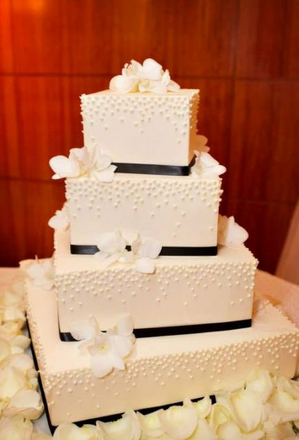 a textural white square wedding cake decorated with black ribbons and white blooms