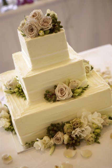 a white textural wedding cake topped with fresh blooms, berries and greenery