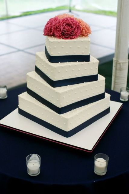 a white beaded wedding cake with black ribbons and bright red blooms on top