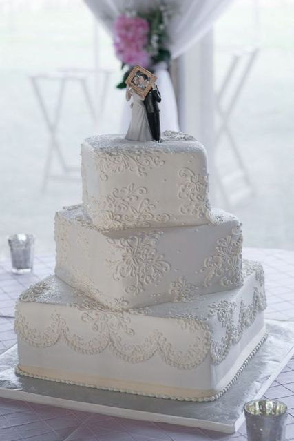 a white patterned wedding cake with a cute figurine cake topper is a very old school idea