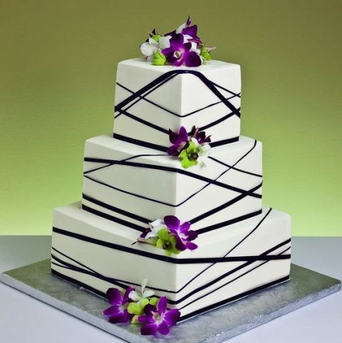 a white square wedding cake decorated with black ribbons and bright purple orchids