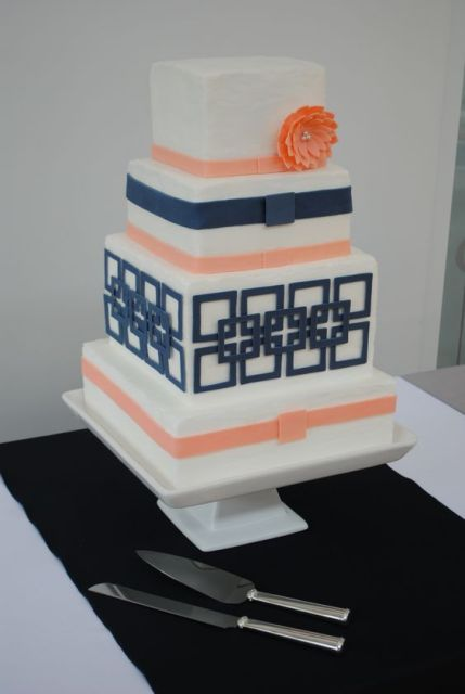 a cute wedding cake in navy and coral plus geometric patterns is a chic idea
