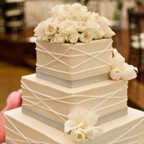 a square wedding cake with patterns, grey ribbons and fresh blooms