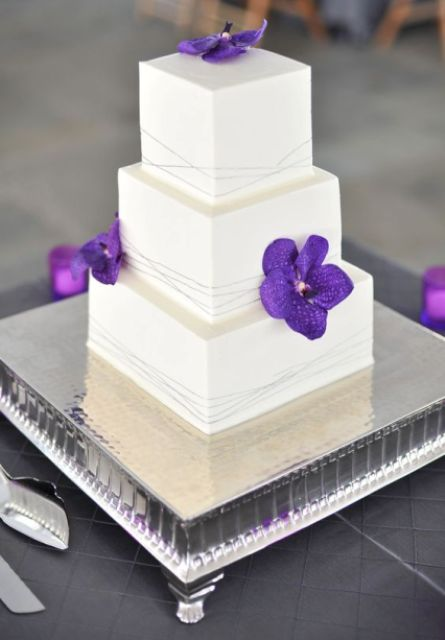 a white square wedding cake with bright purple blooms for a colorful accents