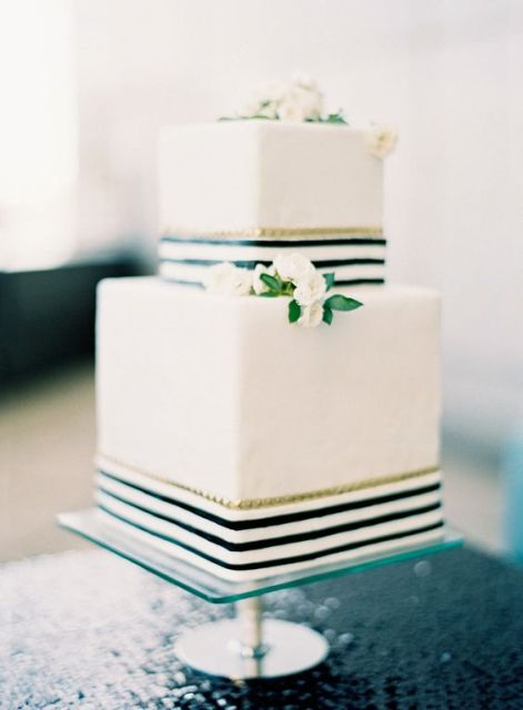 a white square wedding cake with striped black and white ribbons and small white flowers
