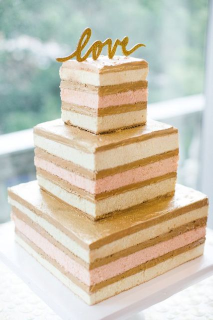 a naked square wedding cake with a simple gold calligraphy topper for a modern wedding