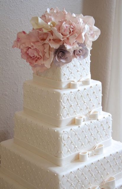 a white formal wedding cake with textural sides and fresh blooms on top