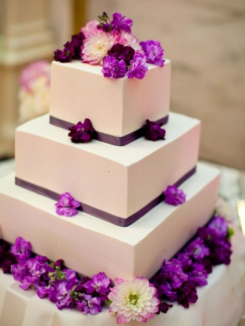 a laconic white square wedding cake with thin ribbons and bright purple flowers