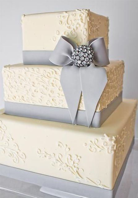 a white square wedding cake with patterns, grey edible ribbons and a large rhinestone piece