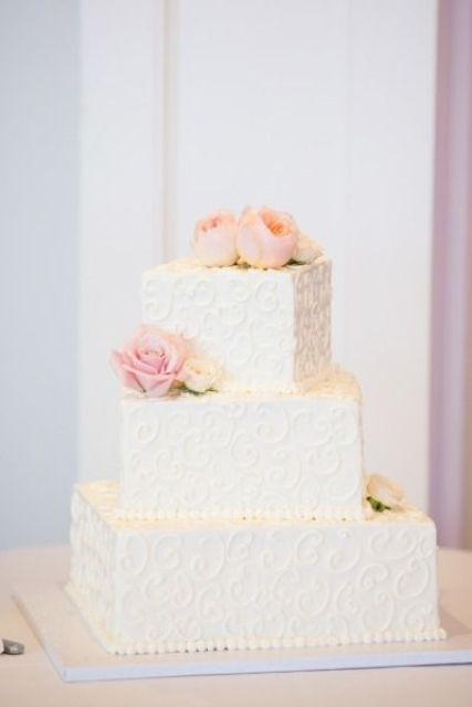 a textural white square wedding cake topped with blush blooms for an elegant wedding
