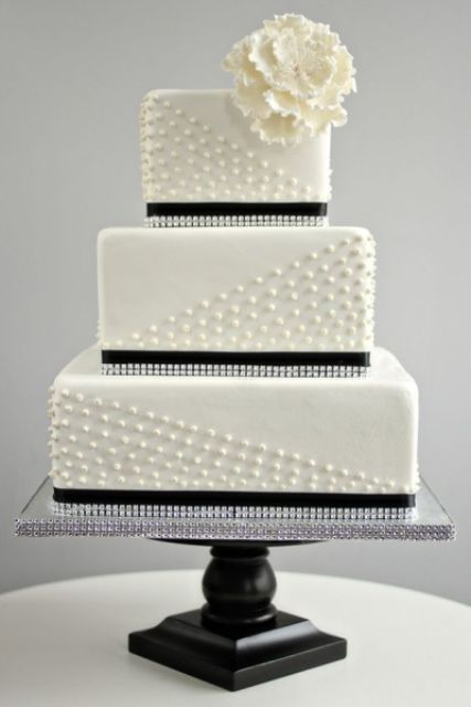 a white wedding cake with white edible beads and black ribbons, rhinestones and a large sugar bloom on top