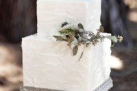 a textural white wedding cake topped with berries and fresh greenery for a modern or rustic wedding