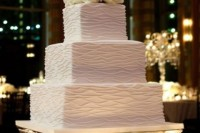 a patterned white wedding cake topped with white roses for a formal wedding