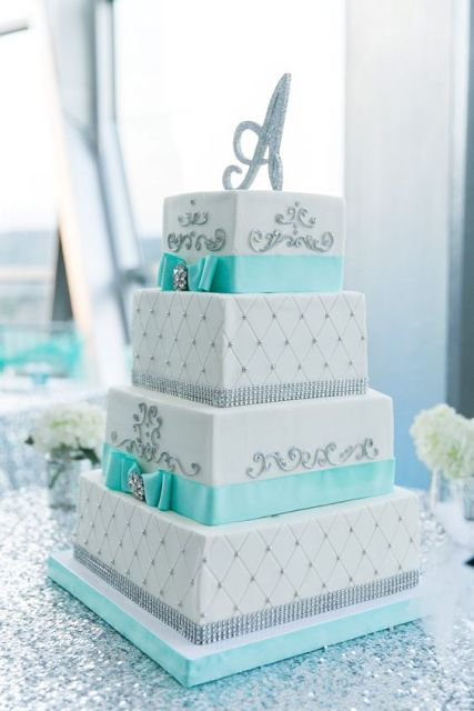 a bright turquoise and white square wedding cake with patterns and turquoise ribbons plus a shiny monogram topper