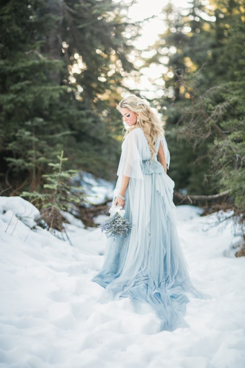 Cinderella bridal look with a layered white and blue wedding gown with a train and short sleeves for a winter wedding