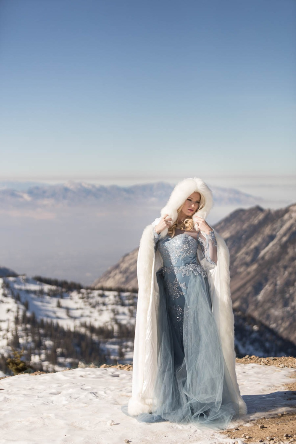 Elsa inspired bridal look with a blue embellished wedding dress with long sleeves and an illusion neckline plus a faux fur coverup with a hood