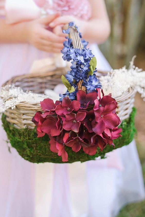 a basket decorated with moss, blue and burgundy blooms is a cool idea for a flower girl