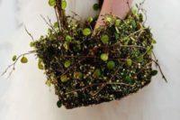 a basket made of moss, foliage and vines looks very wld and woodland-like