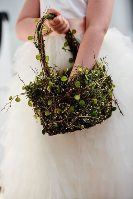 a basket made of moss, foliage and vines looks very wld and woodland-like