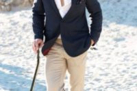 a black jacket, a white shirt, tan pants and grey shoes with no socks for an informal beach groom's look