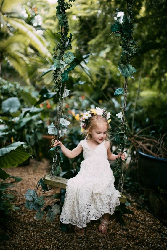 a boho lace A-line flower girl dress with no sleeves and a V-neckline plus flat sandals
