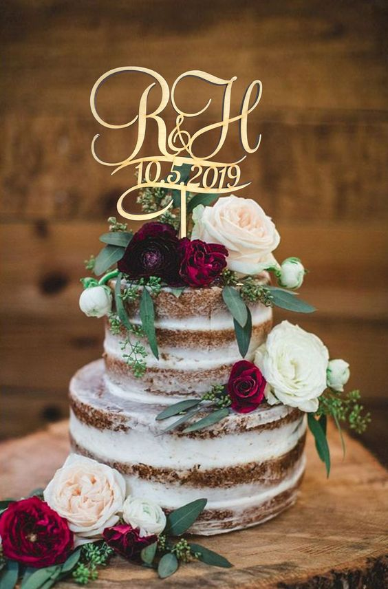 a bold naked wedding cake with neutral and burgundy blooms, with greenery and a calligraphy topper for a summer wedding