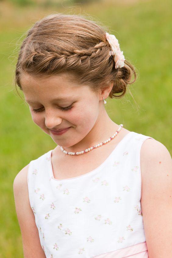 a braided half halo, a low bun, a silk flower headpiece is a chic idea for a lovely flower girl look