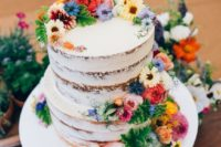 a bright semi naked summer wedding cake with colorful blooms and greenery is an awesome piece