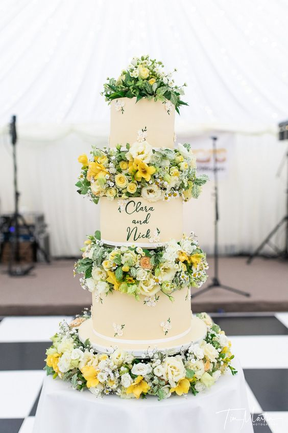 a bright summer wedding cake with floral tiers and white and yellow blooms and greenery between the tiers