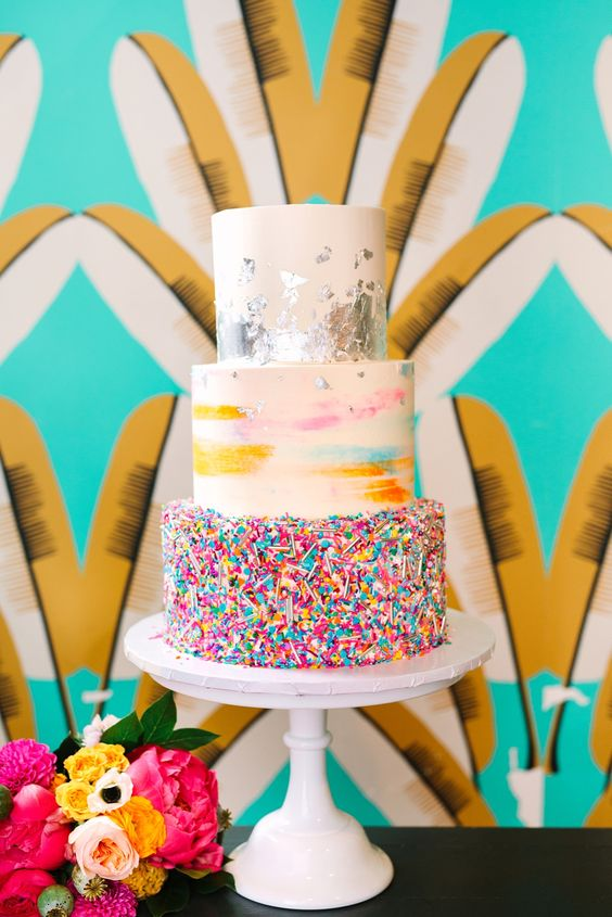 a bright wedding cake with a silver lead tier, a pastel brushstroke tier and a colorful sprinkle tier for a fun wedding
