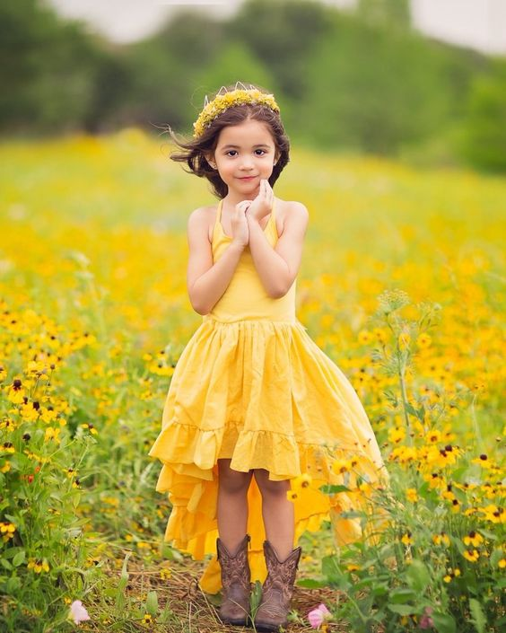 a bright yellow high low maxi dress with spaghetti straps and a ruffle skirt, cowboy boots and a floral crown for a bright rustic wedding