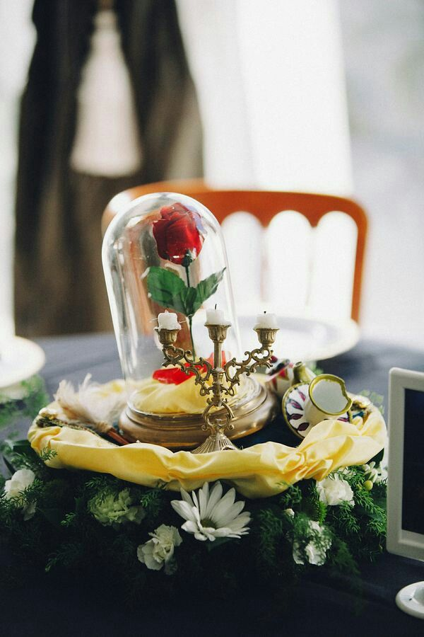 a chic Beauty and the Beast wedding centerpiece with greenery, whiet blooms, gold fabric, candles and a single red rose in a cloche