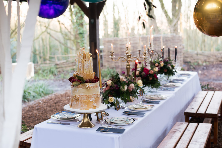 a chic and refined wedding tablescape with candelabras, moody florals, fuchsia candles for the Beauty and the Beast wedding