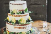 a chic naked wedding cake with fresh citrus slices, blackberries and greenery plus a calligraphy topper