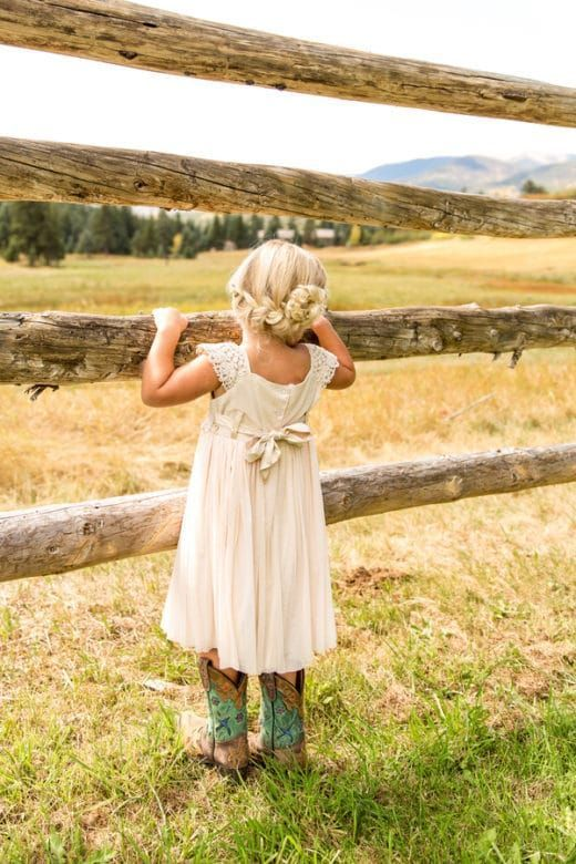 a chic off-white midi dress with lace cap sleeves, a sash, cowboy boots with turquoise detailing and an updo