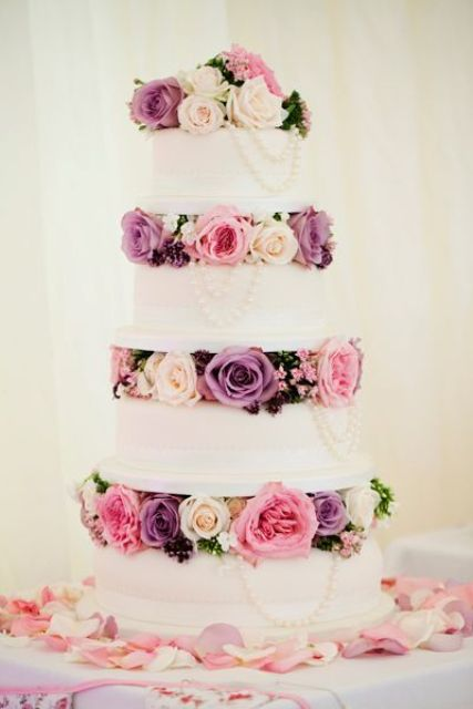 a chic wedding cake with pink, purple and blush blooms and pearls between the tiers
