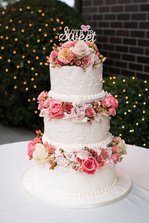 a chic white textural wedding cake with bright pink blooms and berries and a cute topper is wow