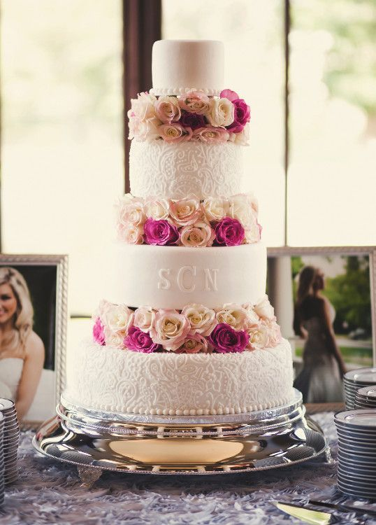 a chic white wedding cake with patterned and monogrammed tiers and neutral and bright blooms between the tiers