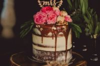 a chocolate drip naked wedding cake with fresh flowers, macarons, greenery and an elegant topper looks chic and yummy