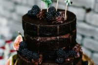 a chocolate naked wedding cake with blackberries, figs and greenery is a great choice for a fall wedding with a boho feel