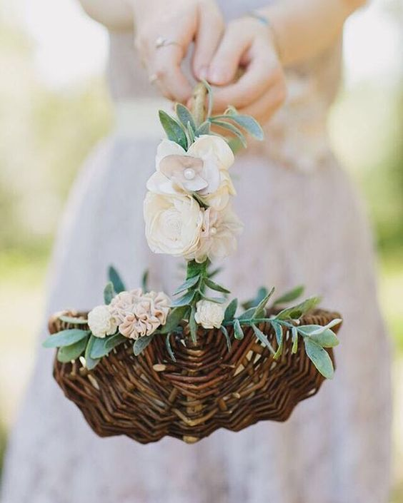 a classic basket with silk white rose petals and greenery is a cool idea for any wedding
